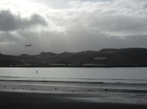 A stand up paddle boarder slowly makes her way across the bay as a jet takes off under mild Southerly conditions. - Lyall Bay, Wellington